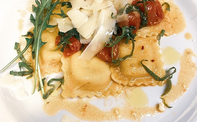 Ricotta and spinach ravioli with Pachino rocket and Parmesan cheese